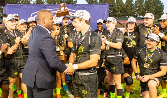 Kevin Battle presenting Life University's Ryan Rees with the D1A Final MVP award in May, 2019. David Barpal photo.