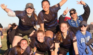 A pyramid of Air Force women's rugby players celebrate victory.