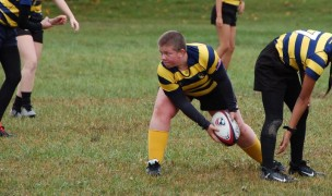 """Cassidy Phillips sends the ball out after a """"tackle"""". Carmel HS Rugby photo."""