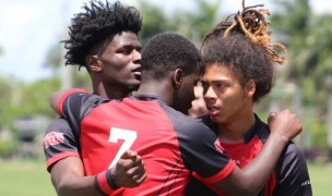 VaShon Mars, Tony Robinson, and Andre Butler hug it out for the Wolverines.